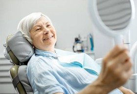 Older woman looking at her smile in dentist's chair