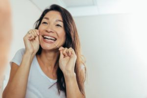smiling person flossing their teeth to keep their dental implants healthy
