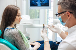 Male dentist explaining dental implant surgery to female patient